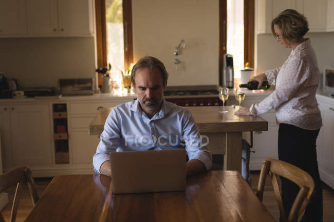 Woman pouring champagne into glass while man using laptop at home — Stock Photo