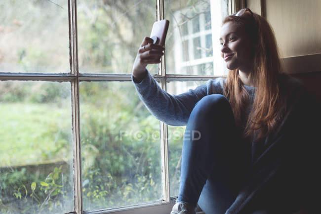 Женщина делает селфи с мобильным телефоном у окна дома — стоковое фото