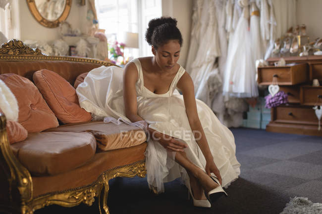 Mixed race bride in wedding dress wearing high heels at boutique — Stock Photo