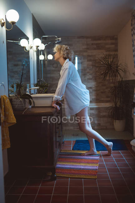 Young woman looking in mirror at bathroom — Stock Photo