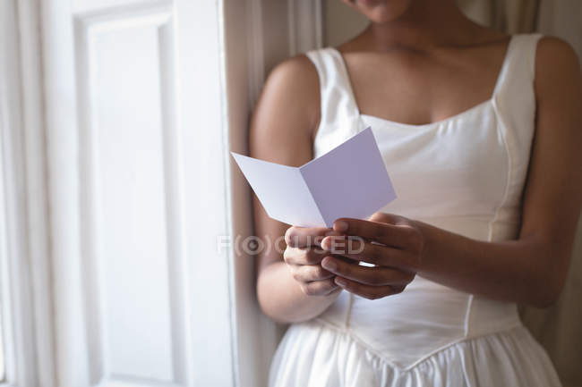 Partial view of bride in wedding dress reading greeting card at window — Stock Photo