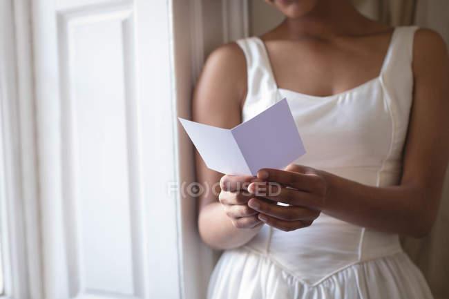 Vue partielle de la mariée en robe de mariée lecture carte de vœux à la fenêtre — Photo de stock