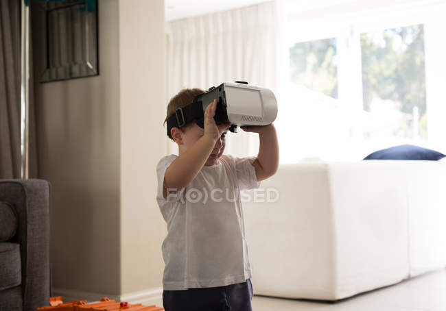 Boy using virtual reality headset in living room at home — Stock Photo