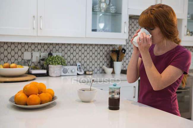 Woman having black coffee in kitchen at home — Stock Photo