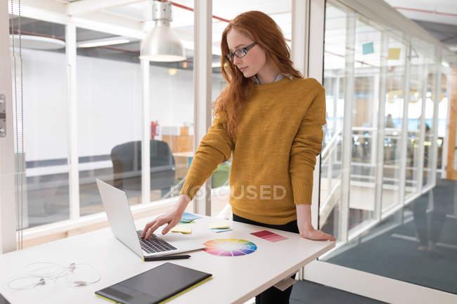 Diseñadora gráfica femenina joven usando portátil en la oficina - foto de stock
