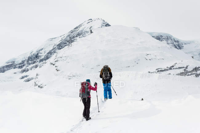Rückansicht eines Paares, das im Winter auf einem schneebedeckten Berg spaziert — Stockfoto