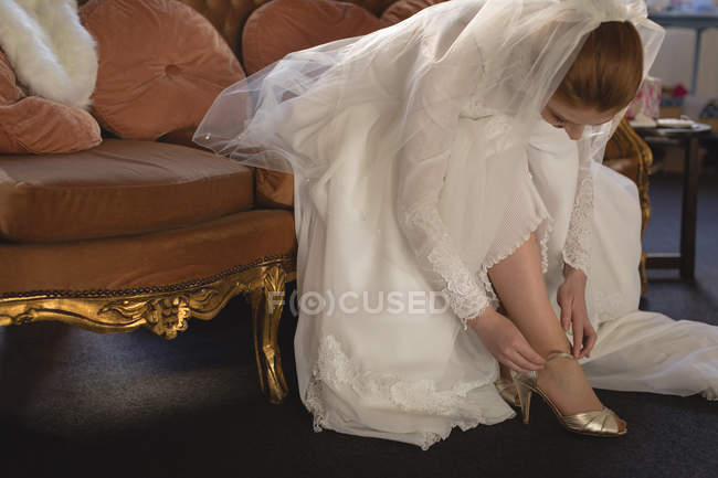 Bride in wedding dress wearing high heels at boutique — Stock Photo