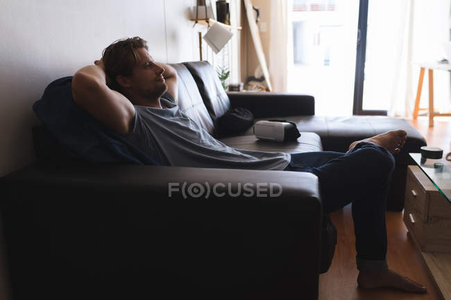 Man Relaxing On Sofa In Living Room At