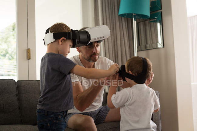 Father helping his son in using virtual reality headset in living room at home — Stock Photo