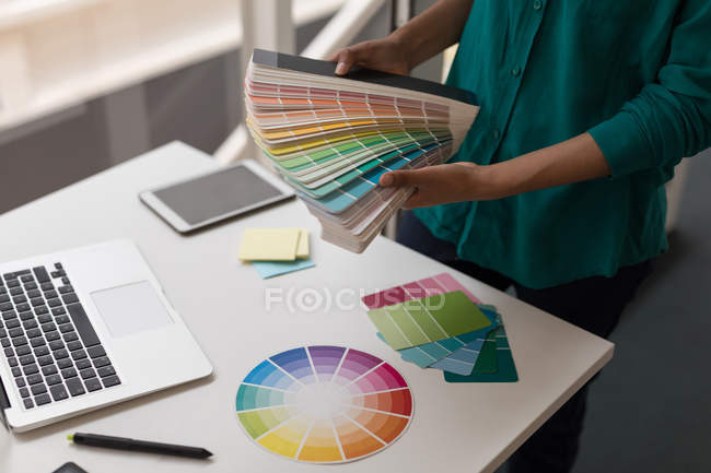 Female graphic designer holding color shade cards in office — Stock Photo