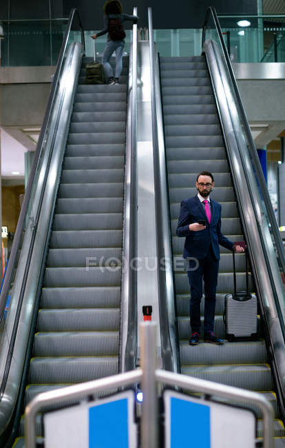 Businessman standing on escalator with luggage at airport — Stock Photo