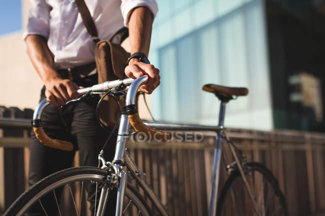 Partie médiane de l'homme d'affaires marchant avec son vélo dans les locaux du bureau — Photo de stock