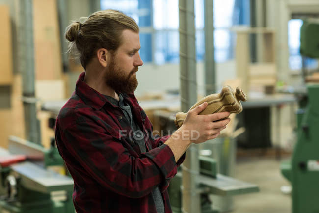 Attentive male carpenter examining a wood furniture at workshop — Stock Photo