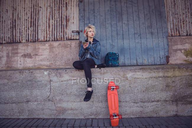 Жінка, що використання мобільного телефону поблизу стежка в місті — стокове фото