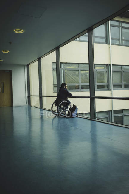 Rear view of handicapped man on wheelchair looking out from glass pane — Stock Photo