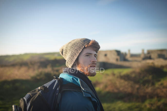 Thoughtful male hiker standing with backpack at countryside — Stock Photo