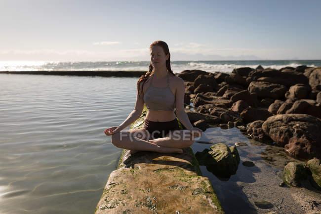 Приваблива жінка робити медитації біля узбережжя басейн у сонячний день — стокове фото