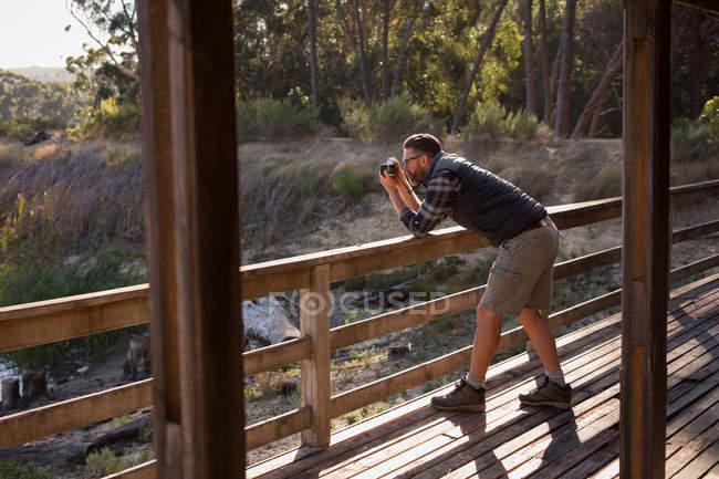 Uomo cliccando foto con fotocamera vintage al portico cabina — Foto stock