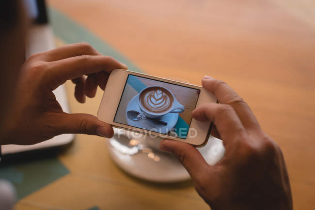 Close-up of businessman clicking photo of coffee in coffee shop — Stock Photo