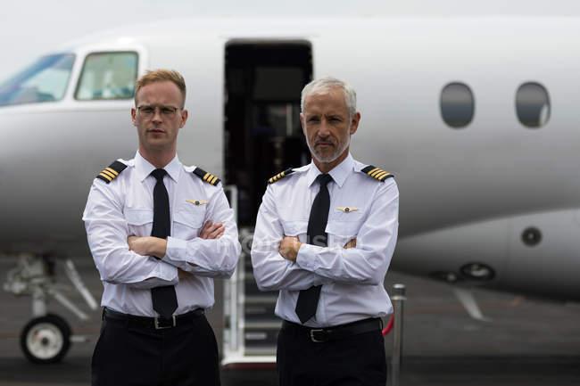 Портрет двух мужчин пилотов, стоя со скрещенными руками — стоковое фото