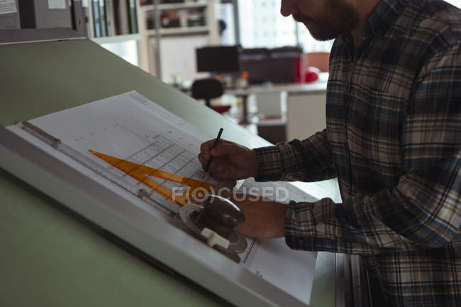 Architect working on blueprint on drafting table in the office — Stock Photo