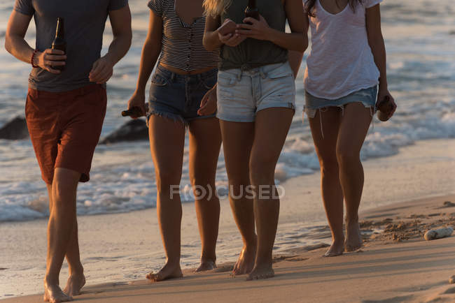 Group of friends walking in the beach at dusk — Stock Photo