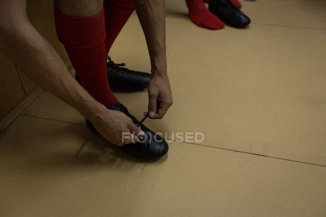 Section basse du joueur de football attachant sa dentelle de chaussure dans le vestiaire — Photo de stock