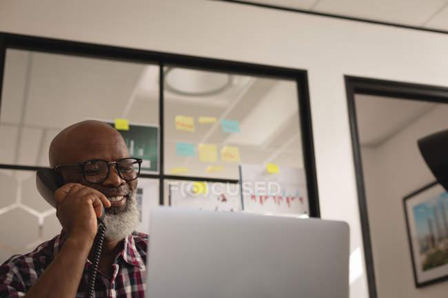 Diseñador gráfico senior hablando por teléfono fijo en la oficina - foto de stock