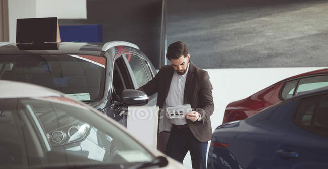 Salesman standing next to car and reading brochure at showroom — Stock Photo