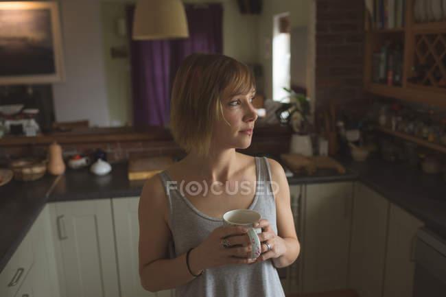 Donna premurosa che tiene una tazza di caffè in cucina a casa — Foto stock