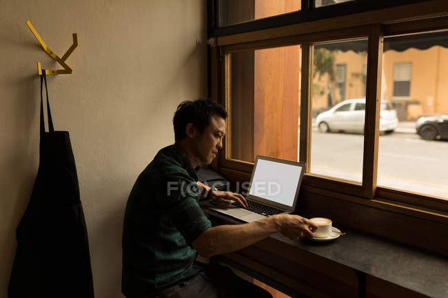 Businessman using laptop while having coffee in the cafe — Stock Photo