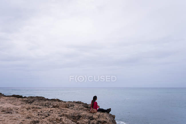 Woman relaxing on a rock in the beach on a sunny day — Stock Photo