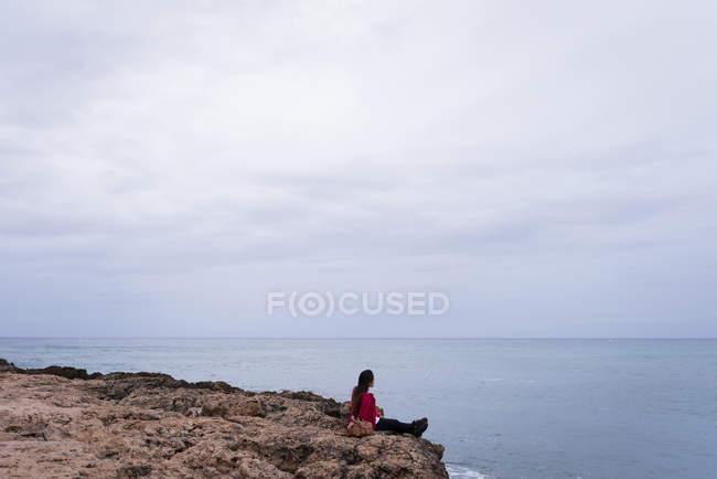 Donna che si rilassa su una roccia in spiaggia in una giornata di sole — Foto stock