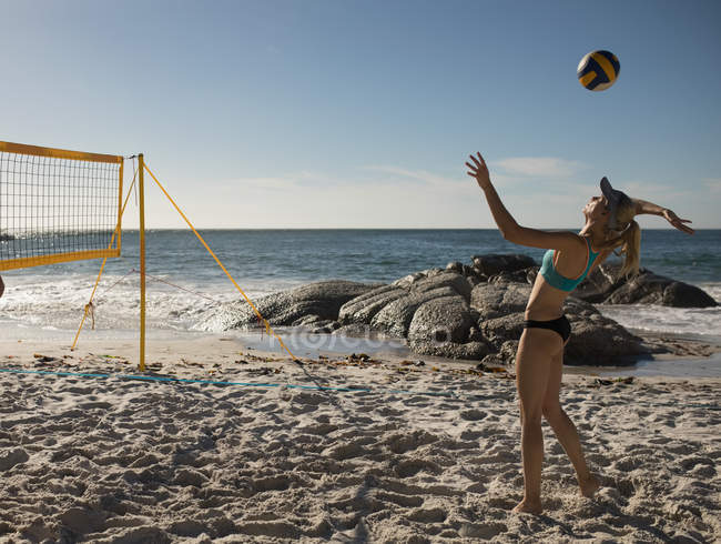 Female volleyball player playing football on the beach — Stock Photo