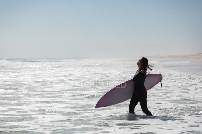 Female surfer standing with surfboard in the beach on a sunny day — Stock Photo