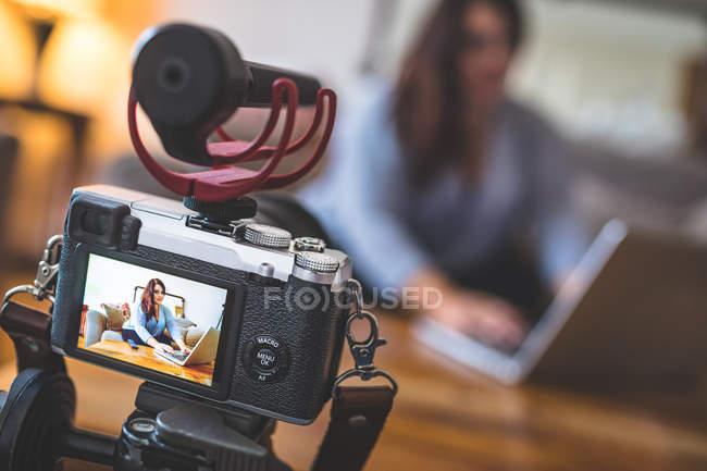 Close-up de fêmea vlogger sentado no sofá enquanto usando laptop — Fotografia de Stock