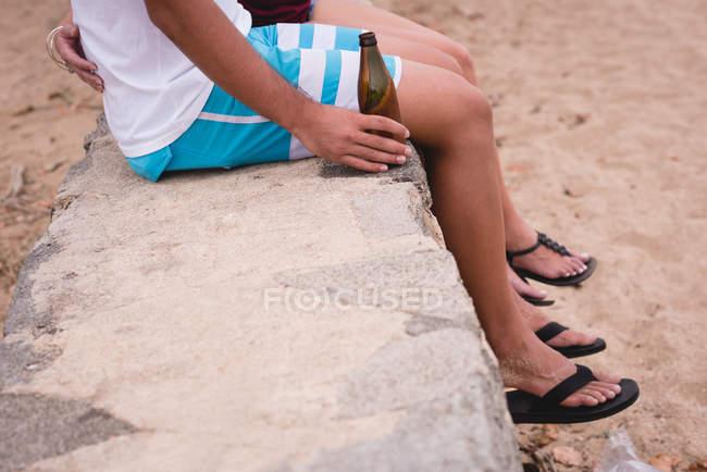Niedriger Teil eines Paares, das zusammen am Strand sitzt — Stockfoto