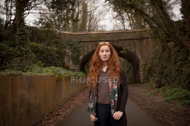 Belle femme debout sur une route de campagne — Photo de stock