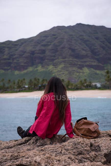 Vue arrière de femme reposante sur un rocher dans la plage — Photo de stock