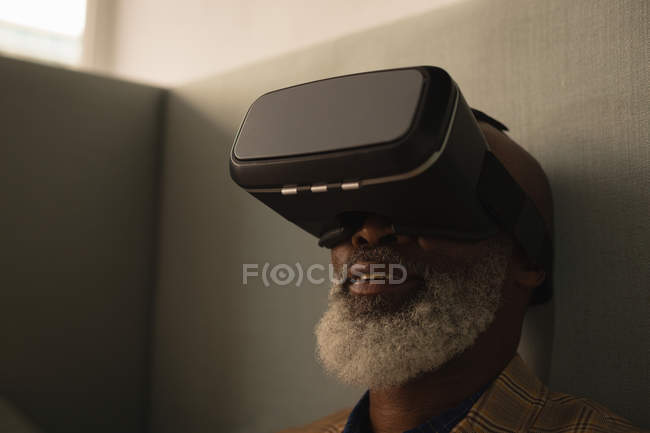 Senior graphic designer using virtual reality headset in cafeteria at office — Stock Photo