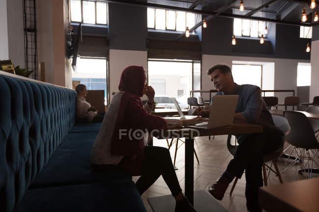 Колегами по бізнесу, які взаємодіють один з одним в кафетерії в офісі — стокове фото
