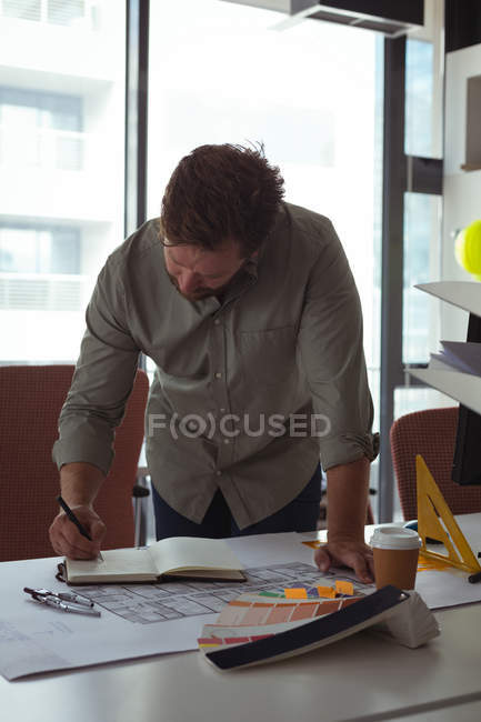 Architect writing note on diary in the office — Stock Photo