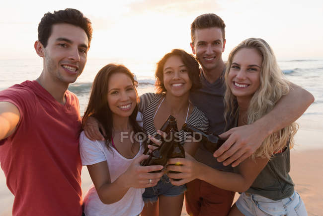 Group of happy friends standing together in the beach — Stock Photo