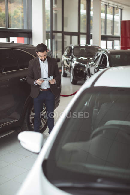 Salesman standing next to car and reading brochure outside the showroom — Stock Photo