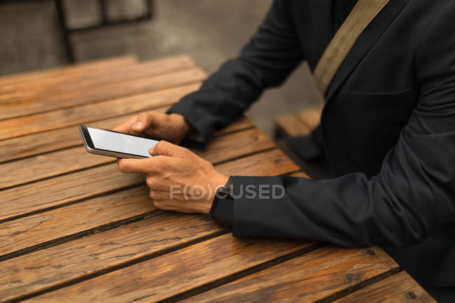 Mid section of businessman using mobile phone in the cafe — Stock Photo