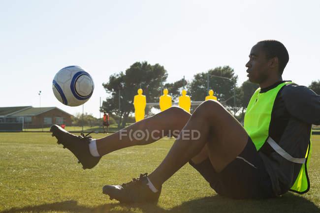 Fußballer übt mit Ball auf dem Feld — Stockfoto