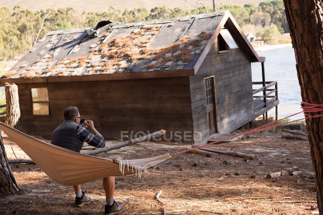 Rear view of man drinking coffee while relaxing on hammock — Stock Photo