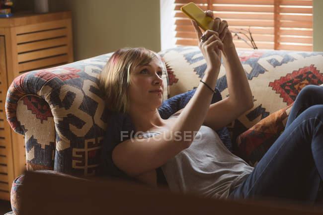 Hermosa mujer tomando selfie en el sofá en la sala de estar en casa - foto de stock