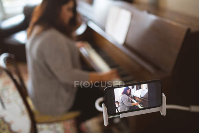 Beautiful female vlogger playing piano at home — Stock Photo