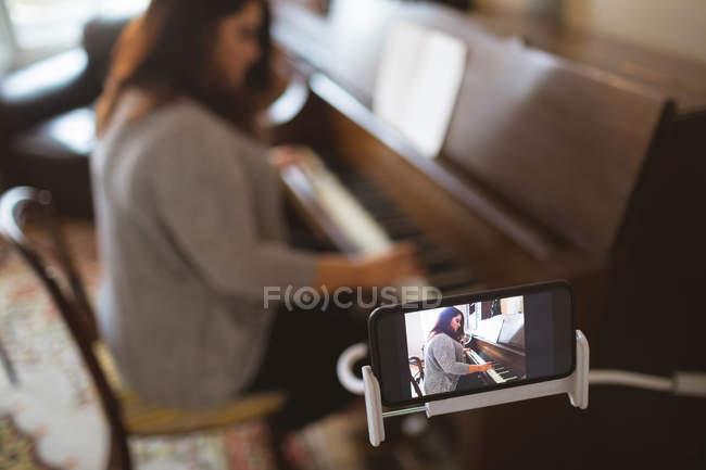 Linda mulher vlogger tocando piano em casa — Fotografia de Stock